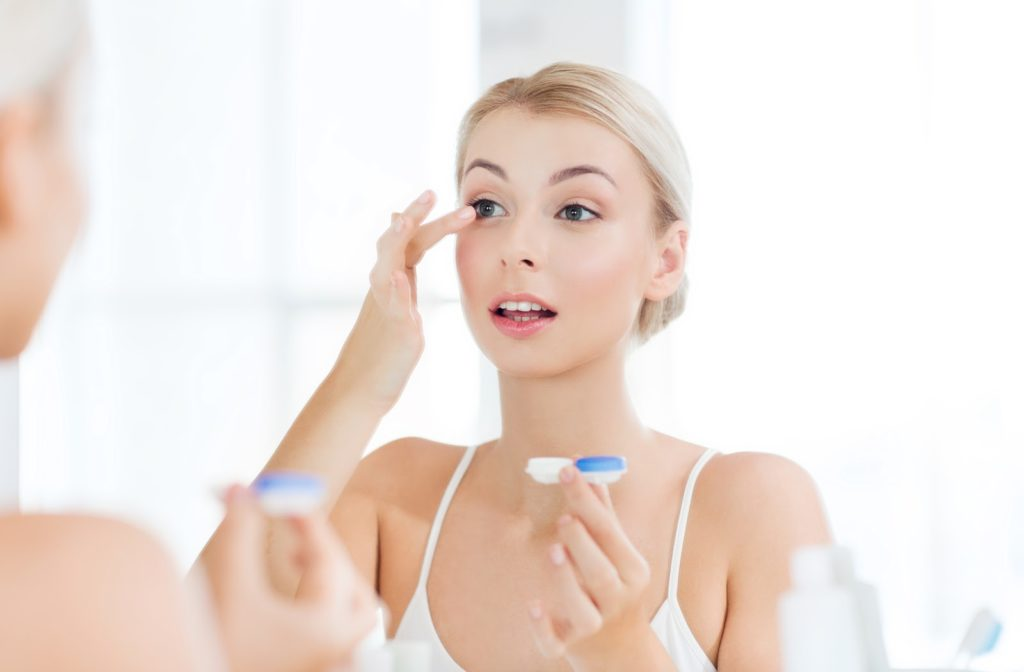 Young woman looking at mirror while putting in contact lens into her eye